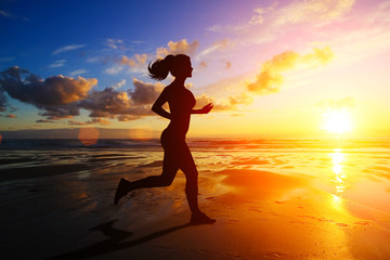 Running girl at sunset silhouette