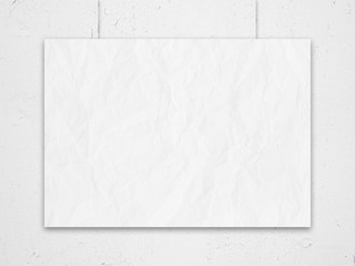 white wall with cracks and crumpled blank list