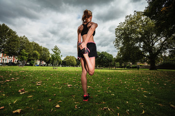 Young woman stretching and working out in park