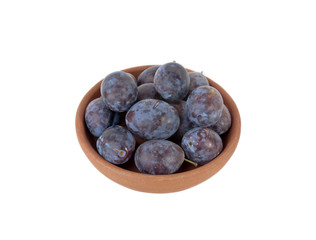 Ripe plums in clay plate isolated on white