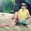 modern hipster girl sitting on a skateboard and inflates gum