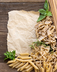 Pasta, herbs and paper on wooden background