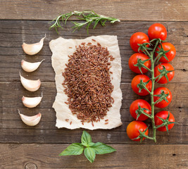 Organic red rice, tomatoes, garlic and herbs on wooden backgroun