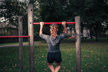 Young woman doing pullups in the park
