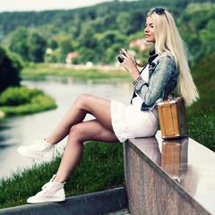 Modern hipster girl photographed vintage camera outdoors.