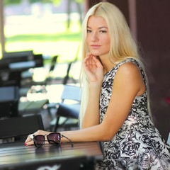 Beautiful girl with sunglasses sitting at a table in summer cafe