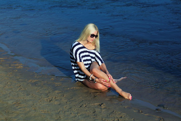 Fashionable  blonde in a striped blouse enjoying on the beach