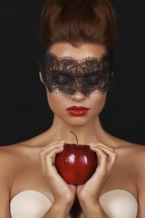 Young beautiful sexy woman with dark lace on eyes with red apple