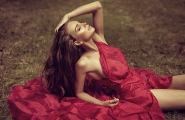Beautiful woman in red dress lying on the grass