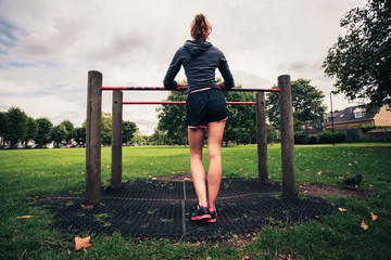 Young woman standing by fitness equipment in the park
