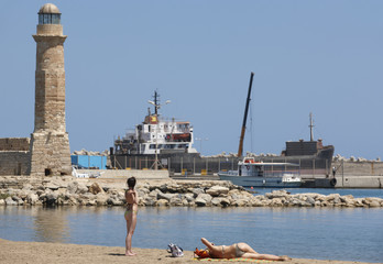 Rethymno port with cargo ships and lighthouse and sunbathers. Cr