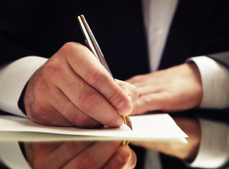 hands of a businessman in a suit signing or writing a document