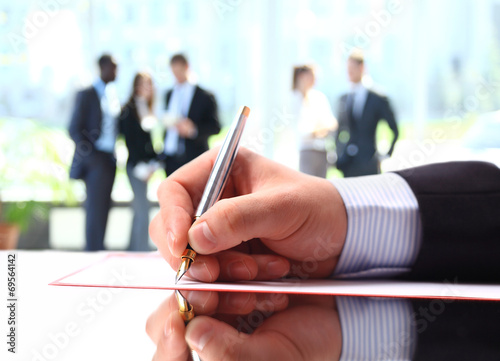 Hands writing on a paper while business team discussing