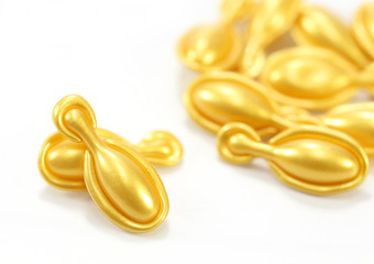 gold cosmetic capsules on white background