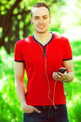 Portrait of happy young man listening to music on smartphone