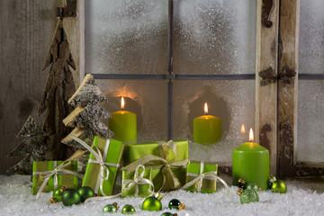 Weihnachtsdekoration in Grün mit Kerzen und Holz im Fenster