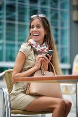 Smiling woman sitting with mobile phone