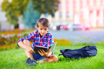 boy, schoolkid reading book in colorful park