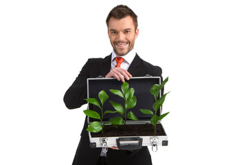 man holding suitcase with plants growing.
