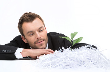 young business man looking at plant and cut paper.