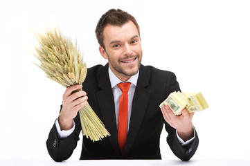 young caucasian man holding fresh wheat and dollars.