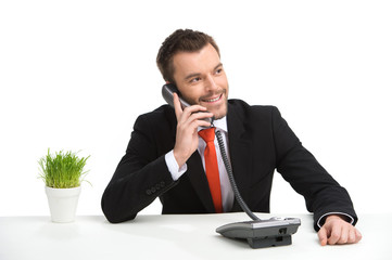 Handsome businessman using landline phone.