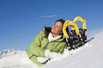 Frau liegt im Schnee , stützte sich auf Schneeschuhen