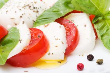 Caprese salad. Mozzarella, tomatoes and basil leaves