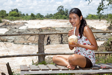 Young woman resting with coconut at the waterfall