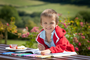 Adorable boy in red sweater, drawing a painting in a book, outdo