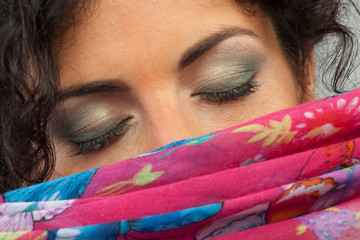 Beautiful woman closing her eyes hiding behind a scarf