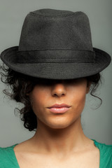 Sexy brunette hiding behind a black hat