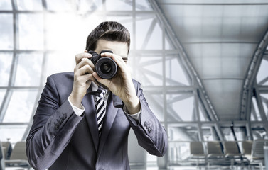 Male photographer focusing and composing an image at the airport