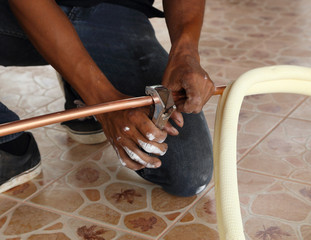 cutting a copper pipe with a pipe cutter