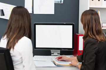 zwei kolleginnen schauen auf pc-monitor