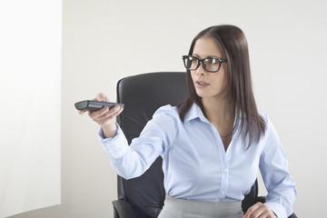 Business-Frau mit Fernbedienung den Kanal wechseln