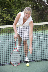 Female tennis reaching over the net to retrieve a ball