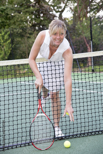 Female tennis reaching over the net to retrieve a ball Poster