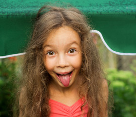 Portrait of an adorable baby girl with tongue sticking out