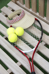 Tennis racquet balls and sun shade on a wooden seat