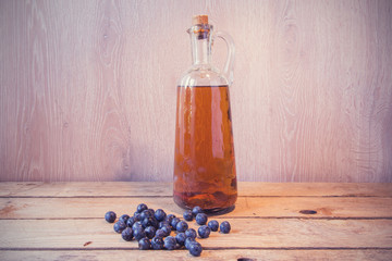 pacharán bottle on wooden table beside sloes
