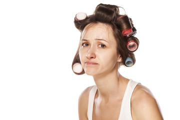 disappointed young woman without makeup and with hair curlers
