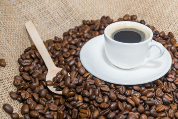 coffee beans with wooden spoon and cup of coffee.