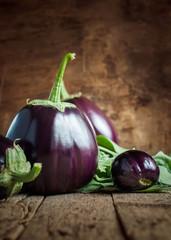 Dark Round Eggplants on the wooden background