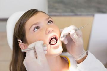 Pediatric dentist examining a little girls teeth