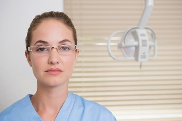 Dentist in blue scrubs looking at camera