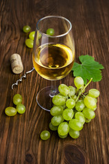 White wine in a glass with vine and grapes