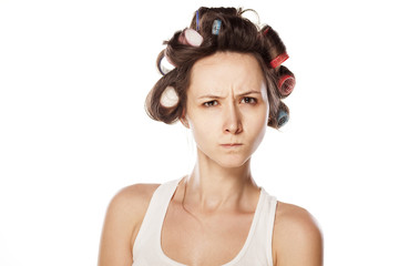 angry and scowling woman without makeup and with hair curlers