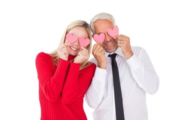 Silly couple holding hearts over their eyes