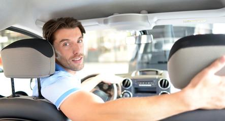 attraktiver Mann schaut sich PKW im Autohaus an